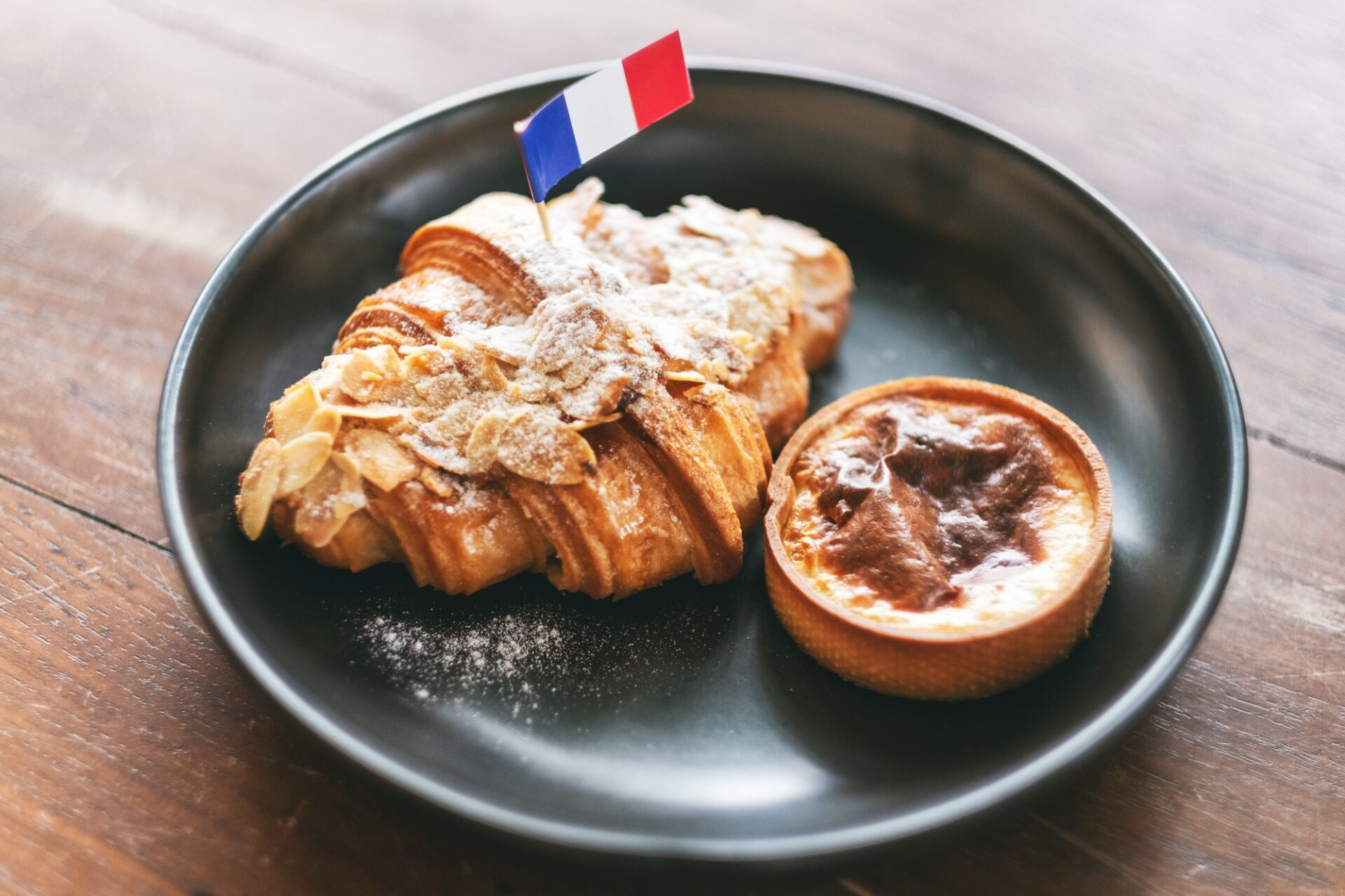A piece of croissant and tart with a flag of France in a black plate on wooden table in cafe